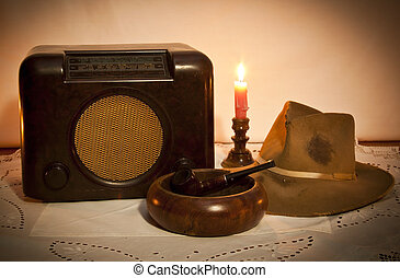 Old radio, hat, pipe and ashtray by candle light on table