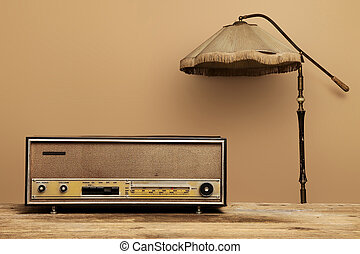 old radio on wooden table with floor lamp