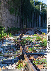 old rails for train a near of stone wall