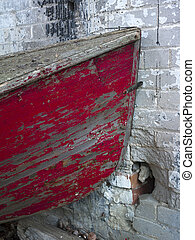old red boat by brick wall