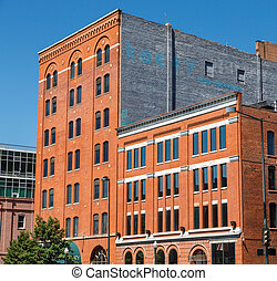 Old Red Brick Buildings with Blue Windows Under Clear Sky