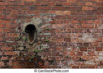 Old red brick wall with pipe