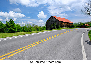 Old red roof barn near highway