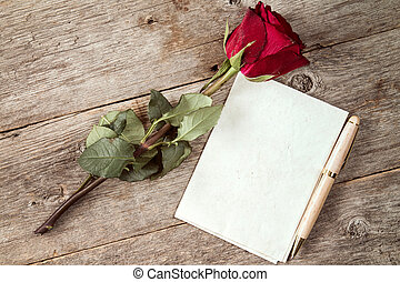 Old red rose and blank paper