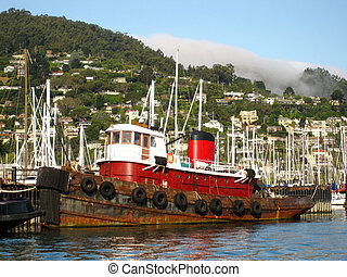 Rusty old red tugboat docked in Sausalito harbor.