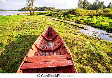 Old red wooden fishing boat at the lake in summer