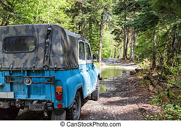 Old reliable jeep of high cross-country standing in forest...