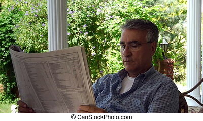Old retired man reading newspaper -