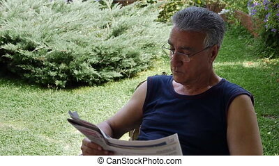 Old retired man reading newspaper