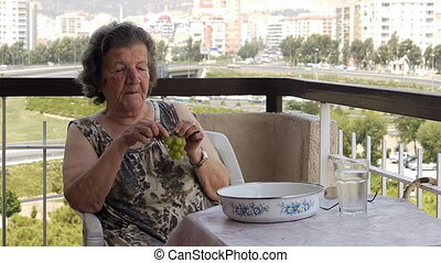 Old retired woman eating grapes