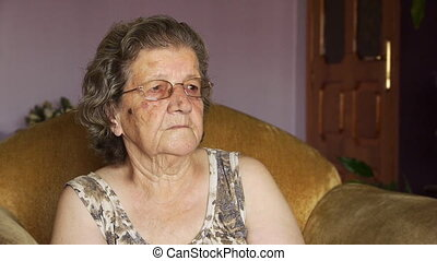 Old retired woman laughing indoors