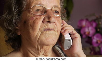 Old retired woman talking on phone