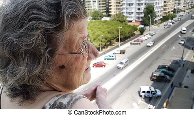 Old retired woman watching traffic