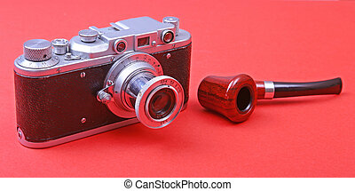 Old retro camera with tobacco pipe on vintage wooden board.