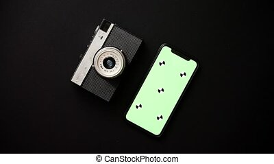 Old retro film camera and modern smartphone on black...