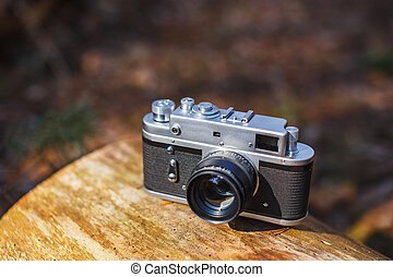 Old retro film camera in a sunny spring forest