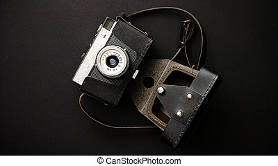 Old retro film camera in leather case on black background