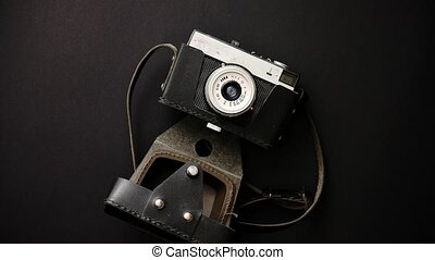 Old retro film camera in leather case on black background....