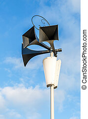 Old retro loudspeakers on the pole against the blue sky