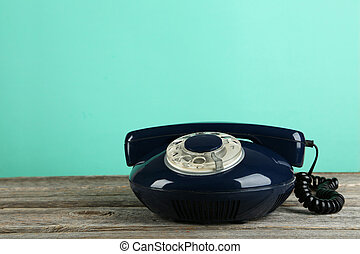 Old retro phone on grey wooden background