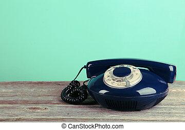 Old retro phone on grey wooden background. Toning