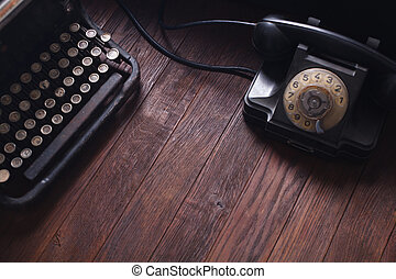 Old retro phone with vintage typewriter and books on wooden board