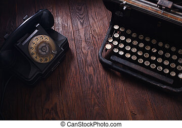 Old retro phone with vintage typewriter on wooden board