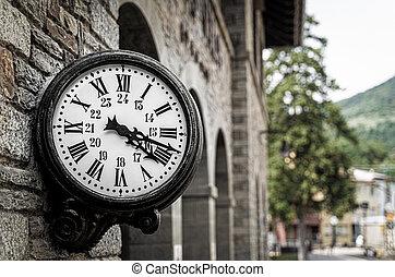 Old retro wall clock at a train station