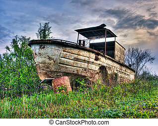 Old, rusty and abandoned river boat in HDR technique