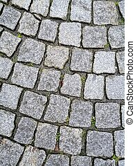 Old road paved with granite stones texture background
