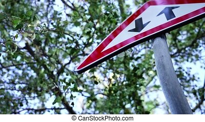 Old road sign Two way traffic in red triangle on grey pole near tree with green leaves on sunny day close low angle shot