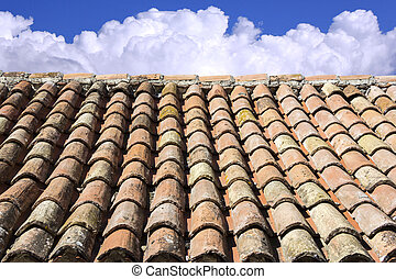 Old roof tiles, blue sky and clouds in the background
