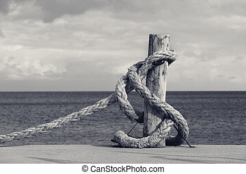 Old rope on seafront, sea and cloudy sky
