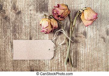 Old roses and blank paper tag.
