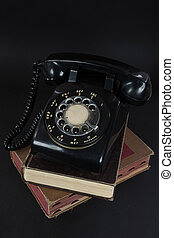 old rotary dial telephone on books