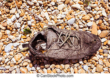 Old rotting lace up sneaker shoe lying on a pebble background in the hot summer sun, view from above