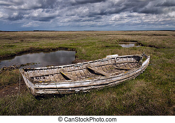 Old rotting wooden stranded rowing boat