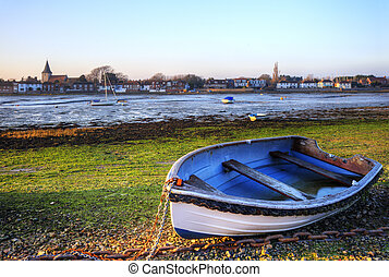 Old rowing boat in low tide harbour landscape at sunset