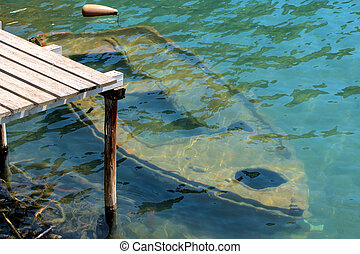 Old rowing boat under water at a wooden jetty - Old rowing...