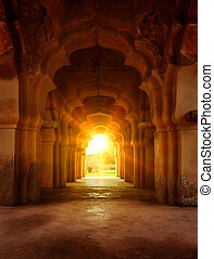 Old ruined arch in ancient palace at sunset, India