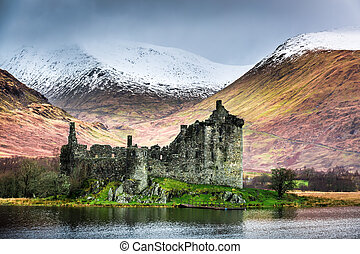 Old ruined castle on the background of snowy mountains