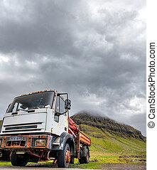 Run-down truck abandoned near the mountains under dark sky