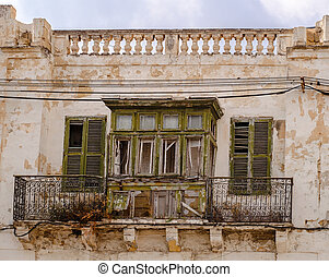 Old ruined window and balcony on a traditional Maltese house.