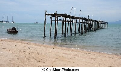 Old ruined wooden pier and boats on sand sea beach, sunny...