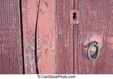 Old run-down red painted wooden door and lock - Closeup of...