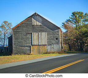 Old Rural Remote Aged Vintage Wooden Warehouse Building along the Street. Barn, Farmhouse, Garage, Storage, Granary, Logistics, Transportation, Industry, and Agriculture concept