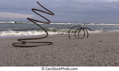 Old rusted iron spring by sea