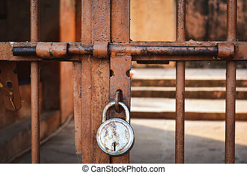 Old rusted metal door with latch and padlock