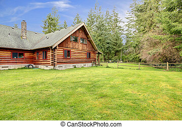 Old rustic American log cabin in the country side.
