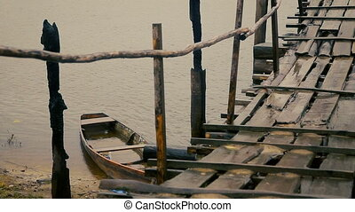 Old rustic bridge and half sank wooden boat in a rainy day...